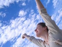 Mujer con los brazos alzados hacia el cielo
